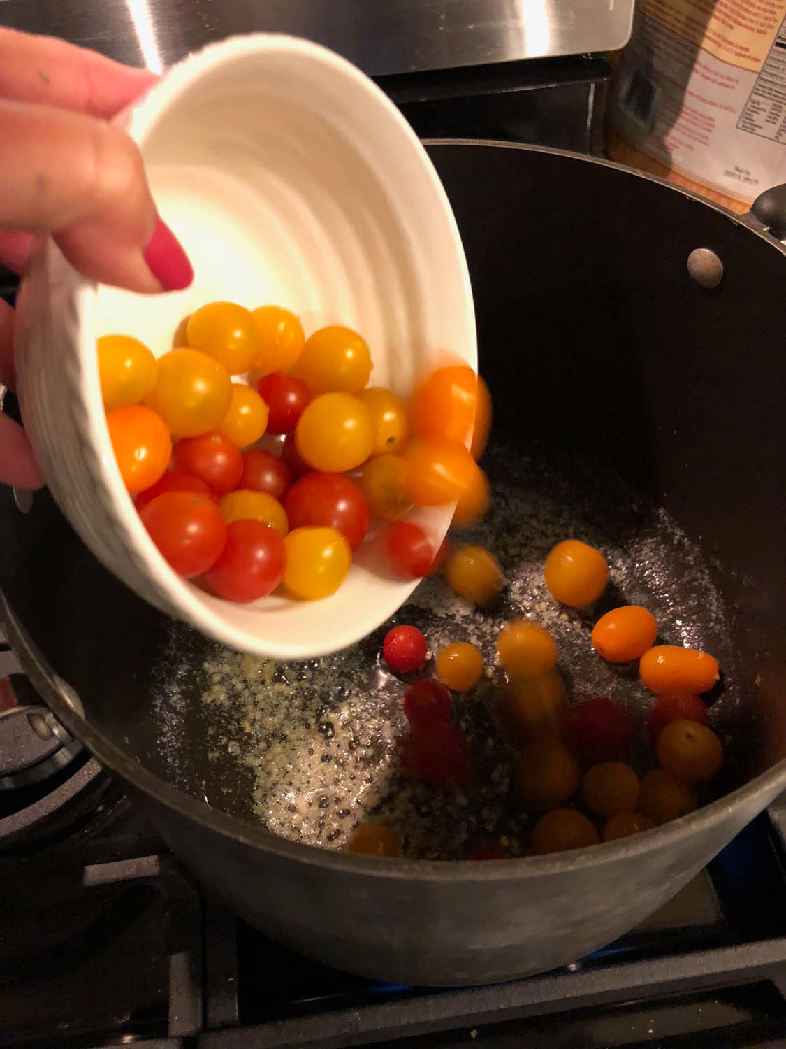 adding tomatoes to pot of melted butter mixture