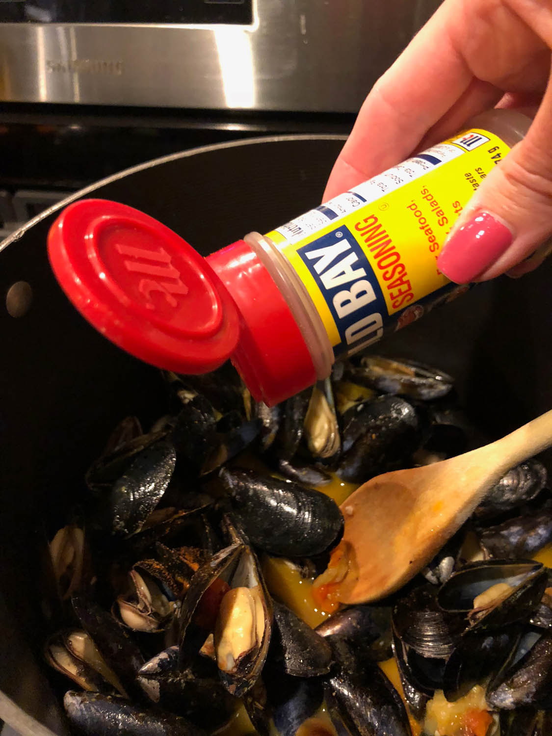 adding old bay seasoning to butter mixture for mussels