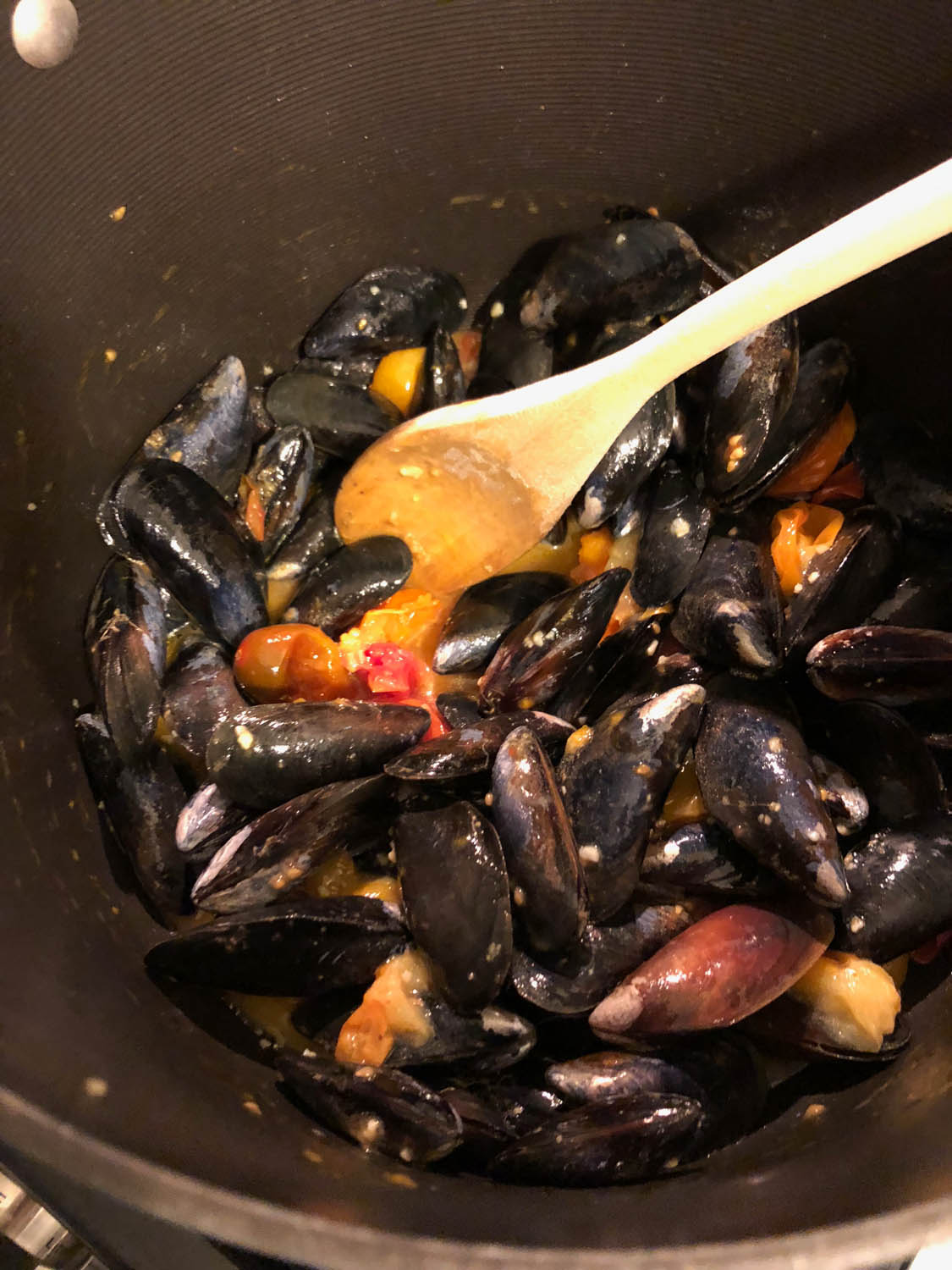 Stir mussels with broth to coat.
