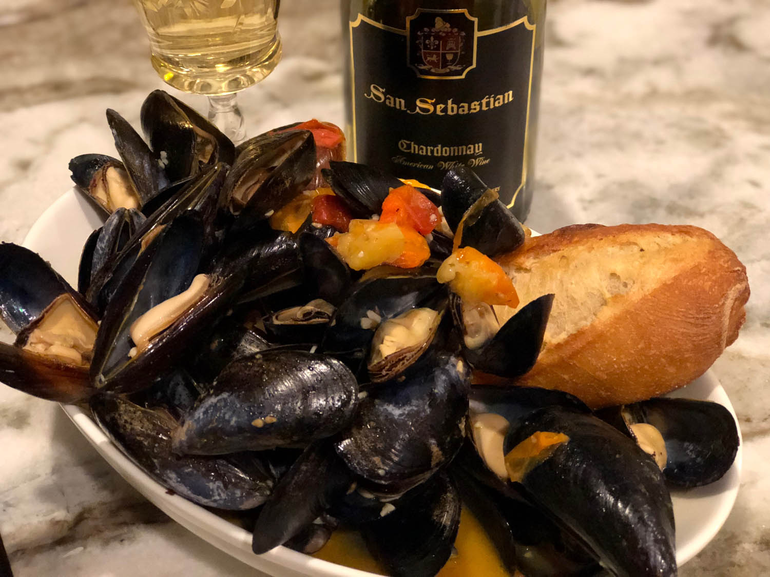 Finished savory mussels with tomatoes and white wine recipe plated and served with fresh, crusty bread.