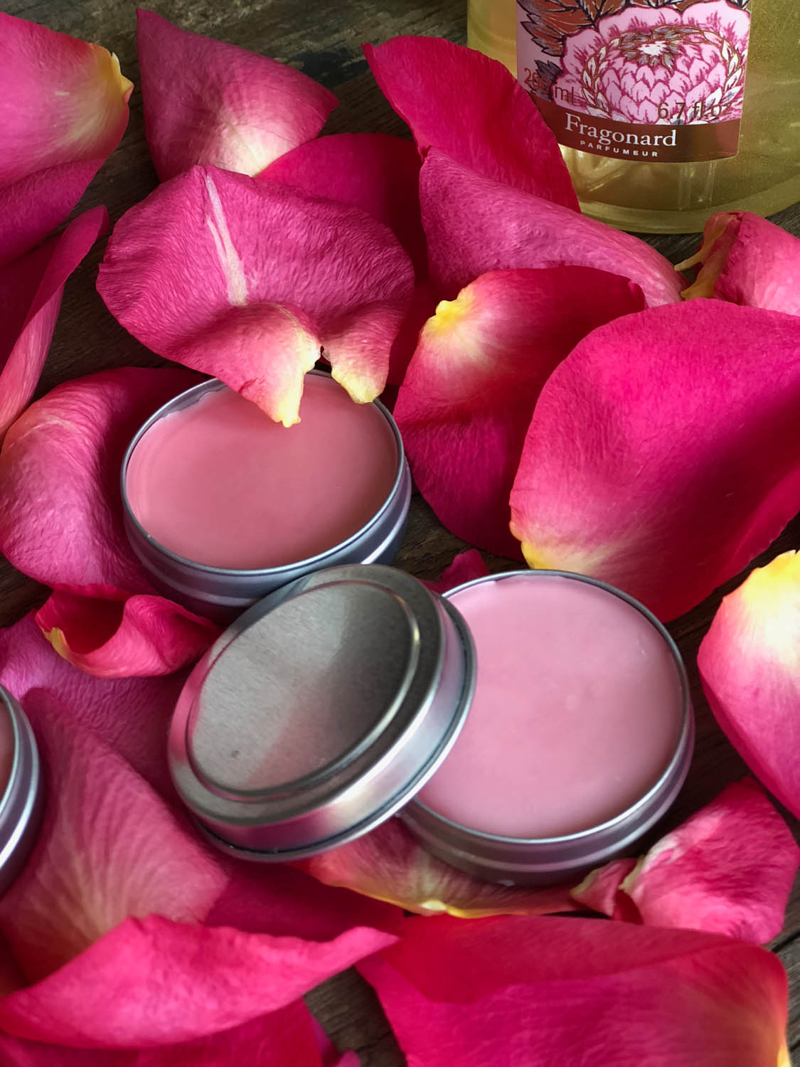 Finished homemade lip balms with pink colorant displayed among rose petals