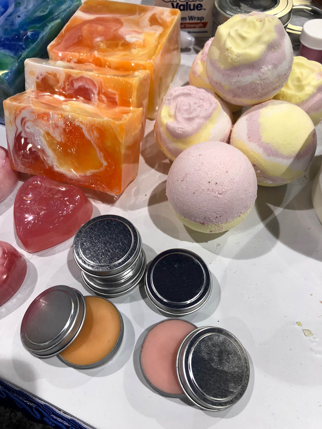 An assortment of homemade glycerin-based soaps, bath bombs, and lip balms made from Life of the Party products.