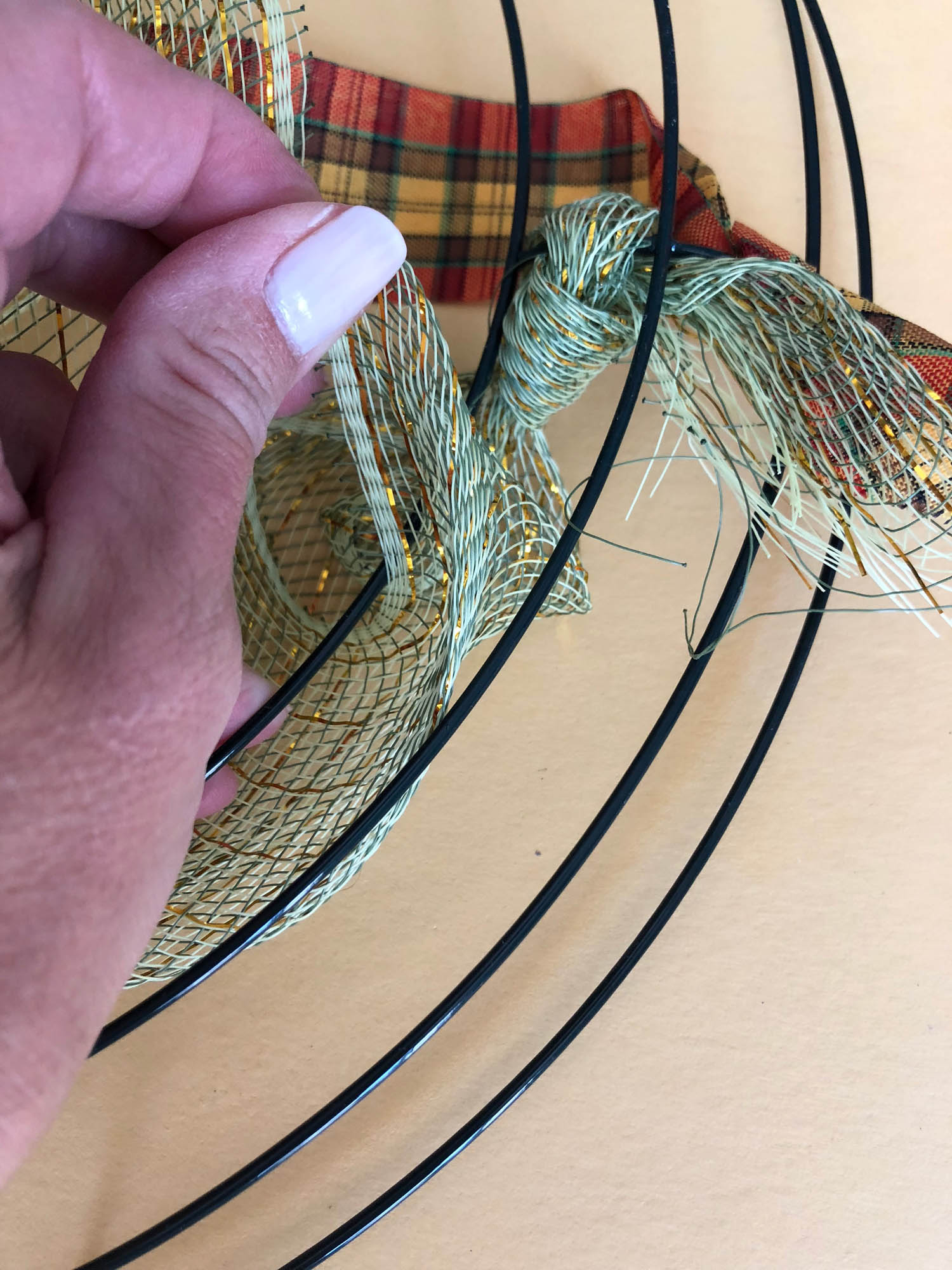 weaving the wired ribbon through the metal wreath frame