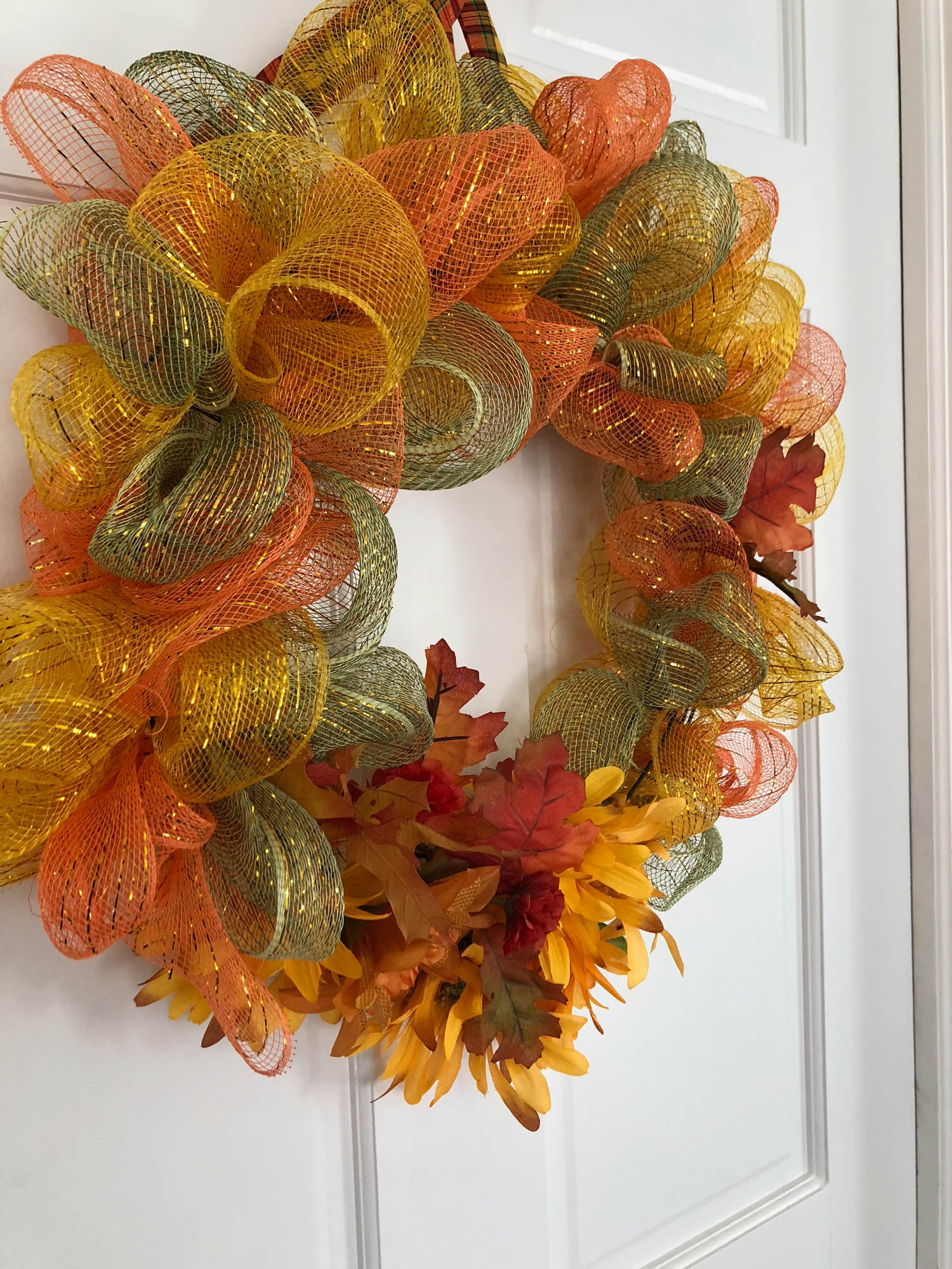 Side view of wired ribbon wrapped wreath hanging on a door