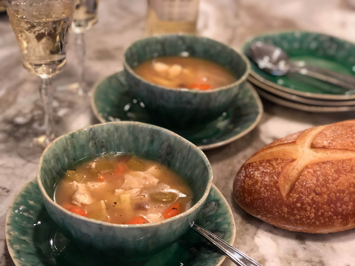 Homemade chicken noodle soup served in bowls with french bread and wine.