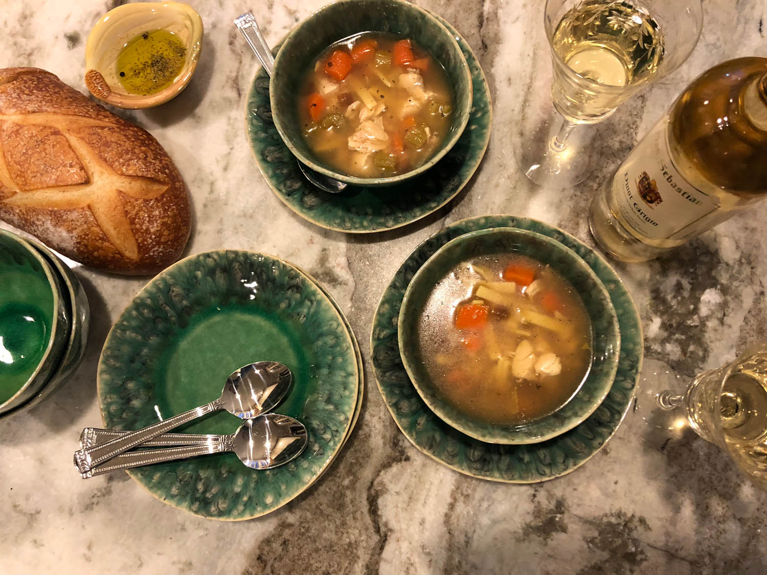 Overhead view of table set with homemade chicken noodle soup recipe served in bowls with loaf of French bread and wine.