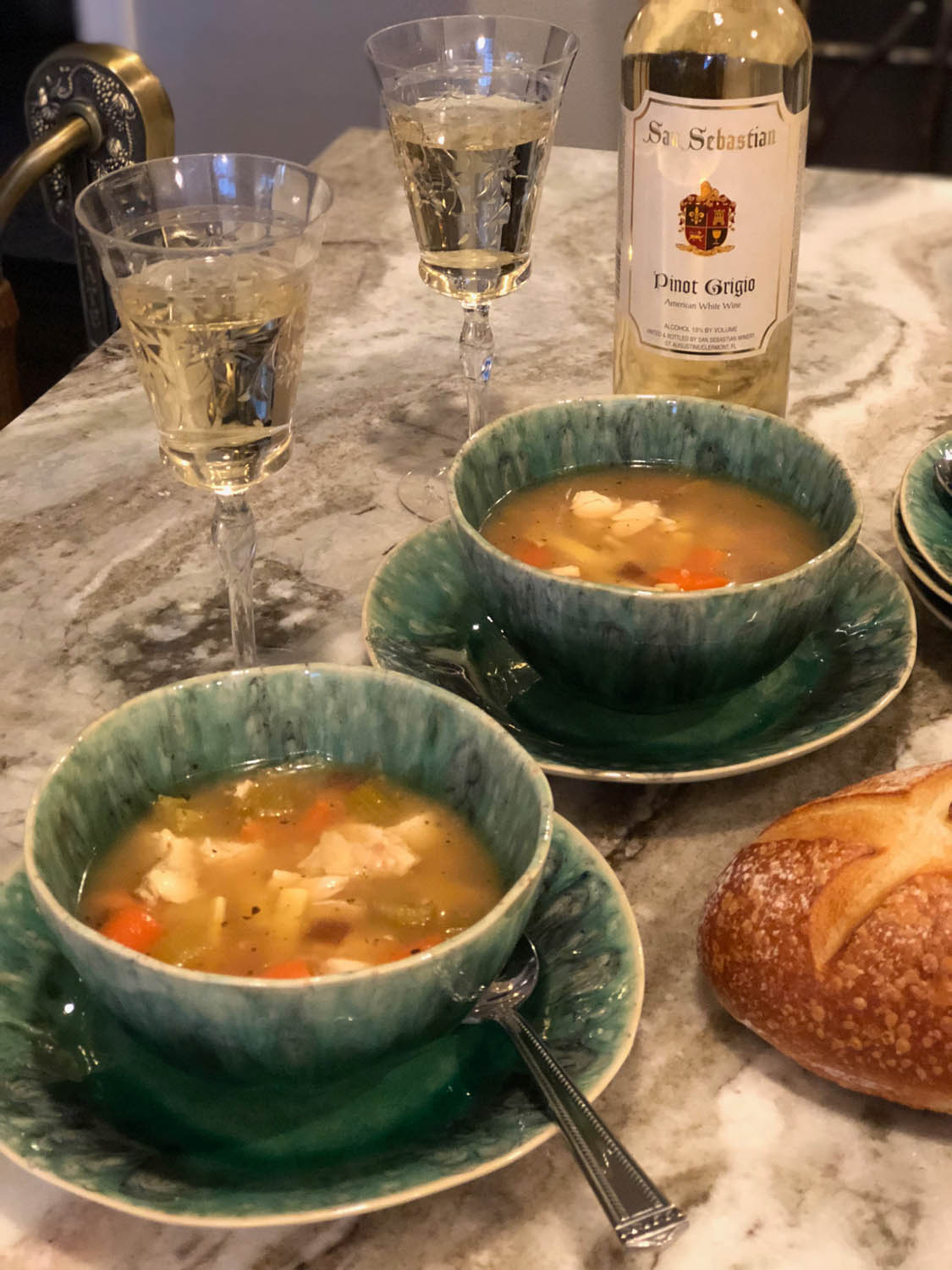 Marble counter set with homemade chicken noodle soup served in bowls and French bread and San Sebastian Pinot Grigio wine.