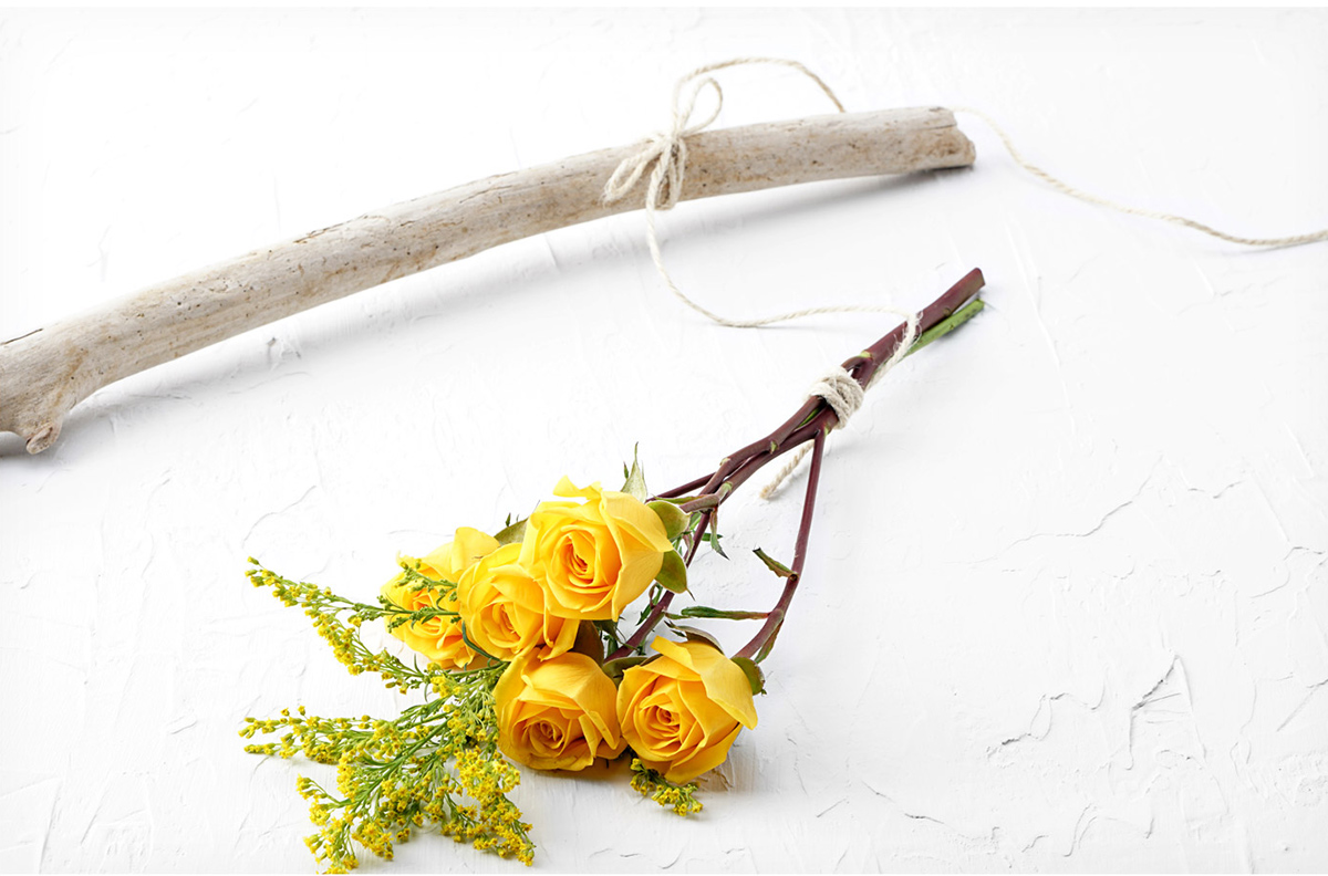 Bundle of fresh flowers tied with string and tied to stick to hang to air dry.