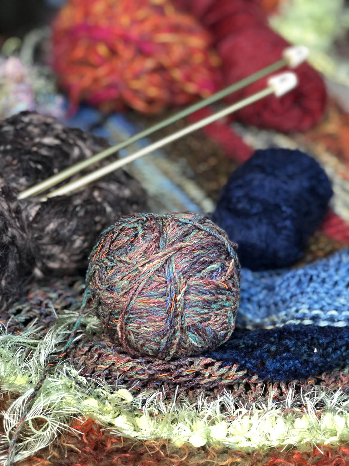 knitting needles in ball of yarn atop knitted throw