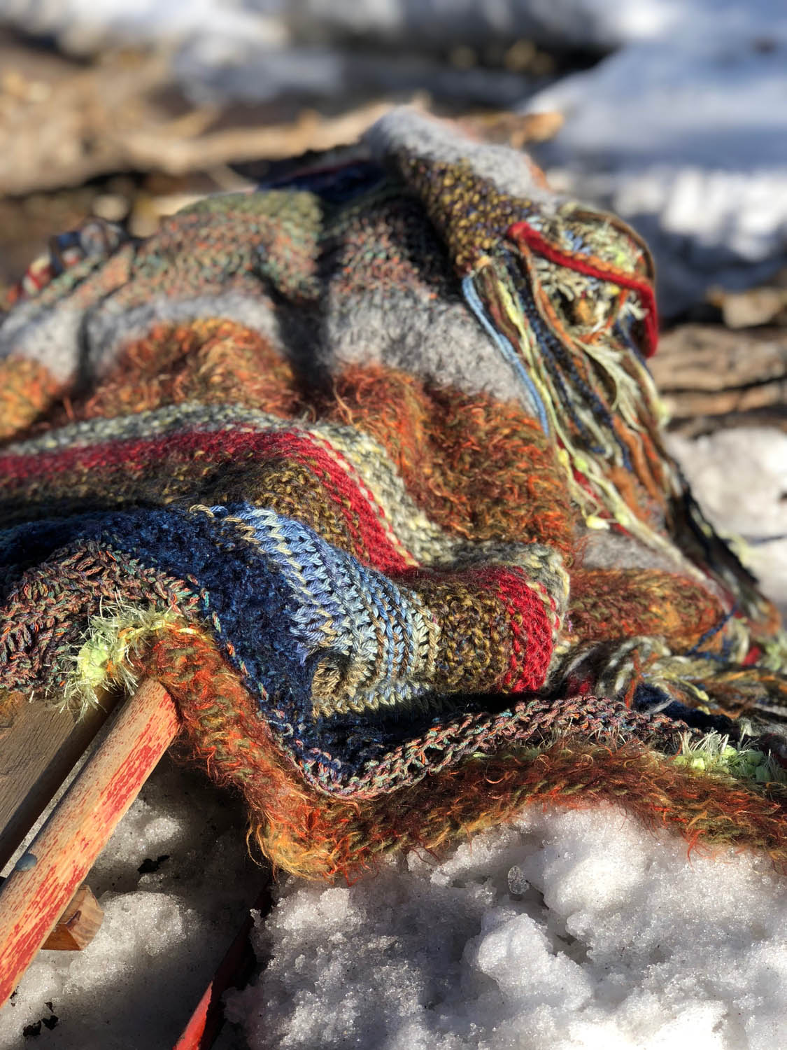 scrap yarn knit throw atop a sled in snow