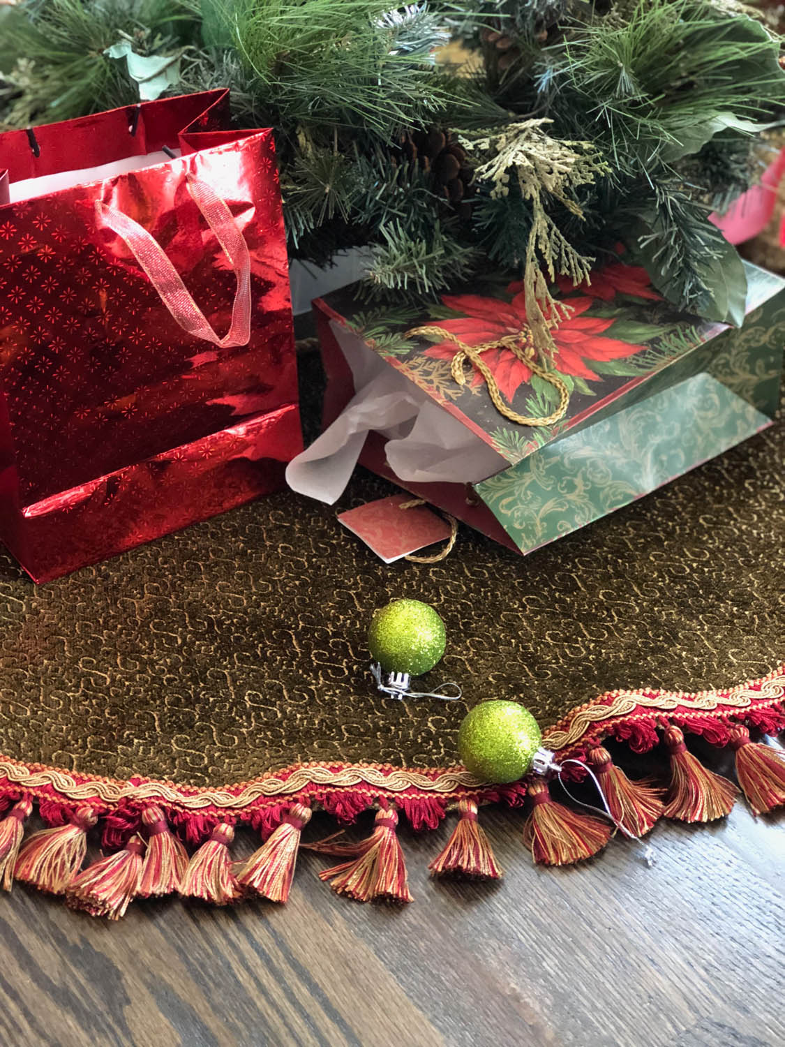 DIY no-sew reversible upholstery fabric Christmas tree skirt under a Christmas tree with scattered gifts and ornaments.