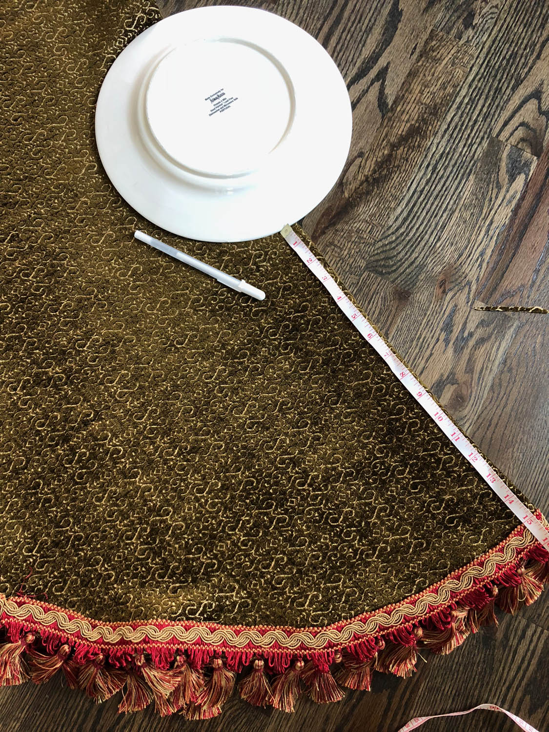dinner plate placed over upholstery fabric to mark center circle opening for Christmas tree skirt