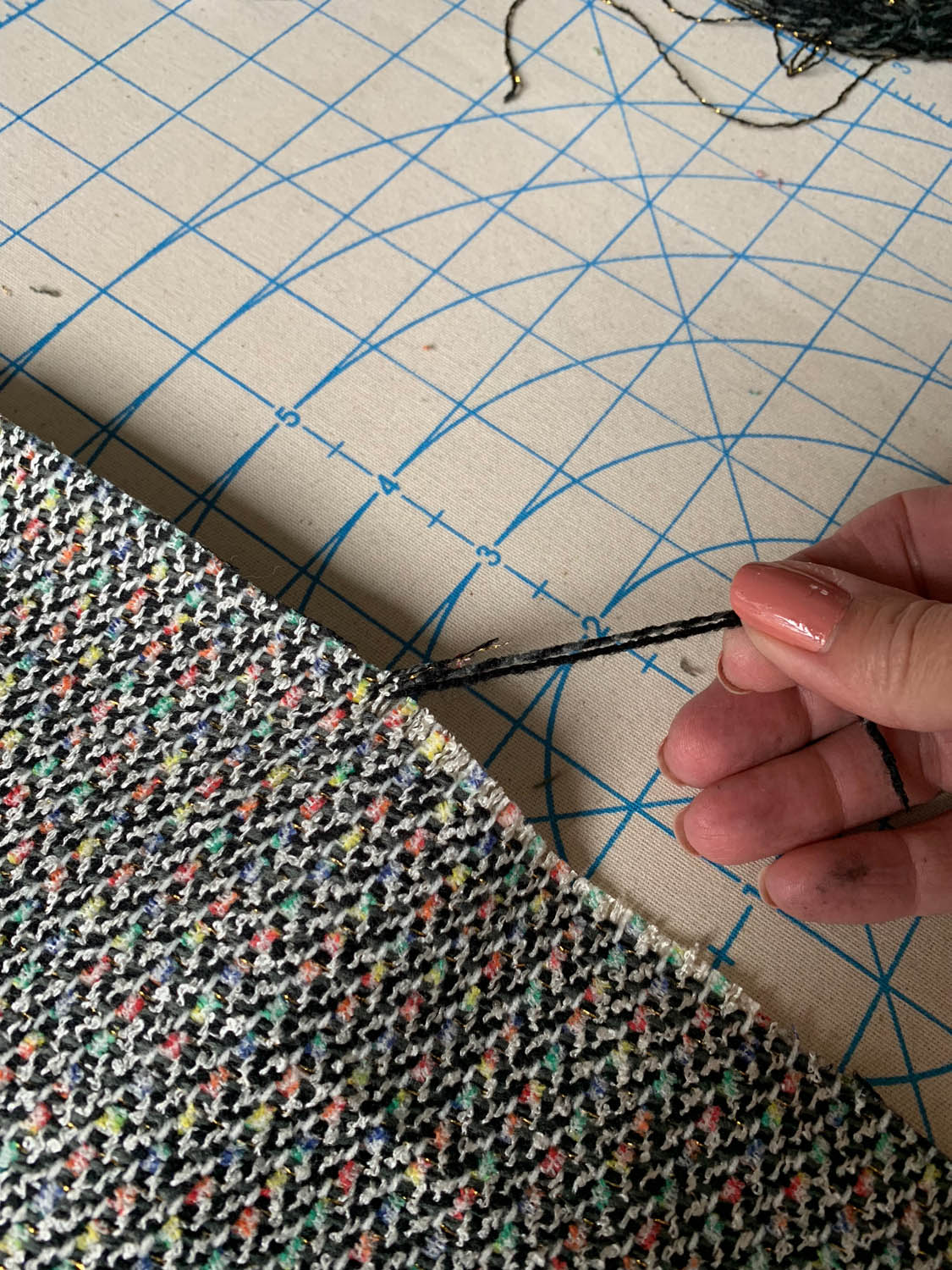 fingers pulling crosswise threads from upholstery fabric for fringe