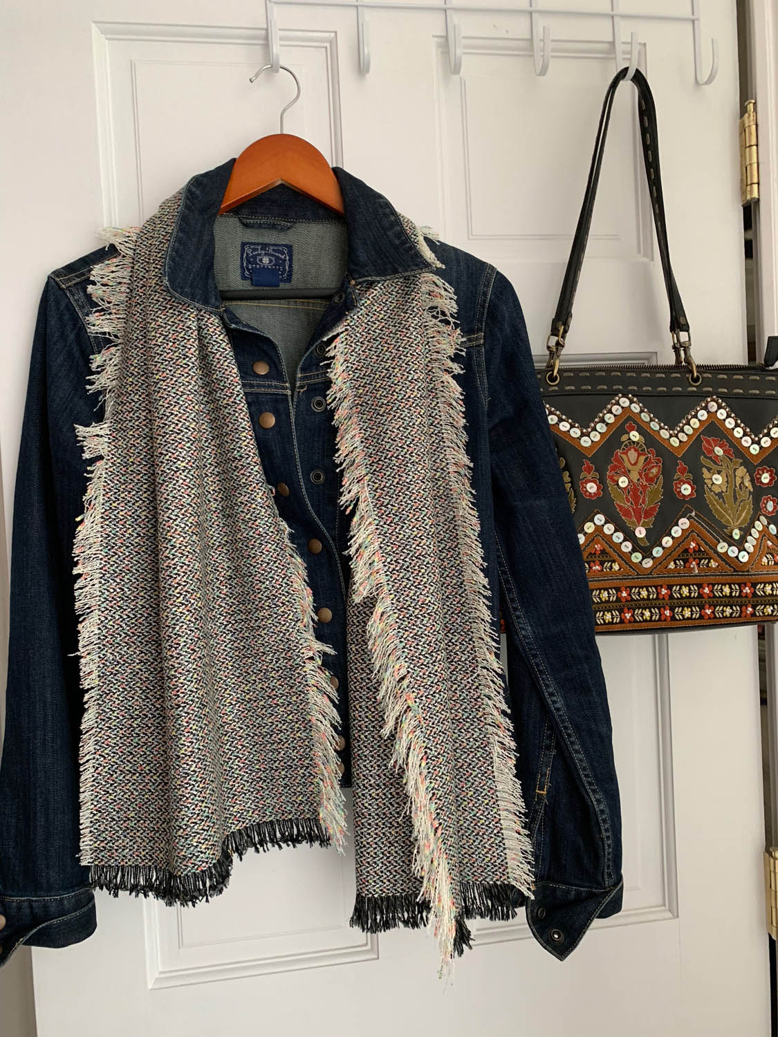 finished no-sew fringed fabric scarf draped over denim jacket on a hanger