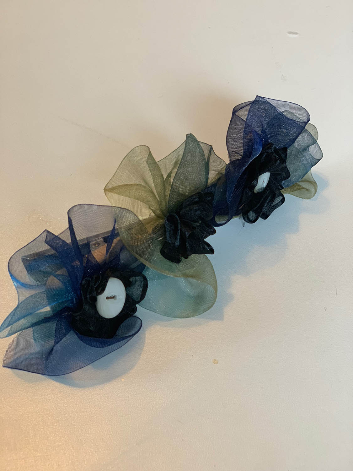 Silk ribbon flowers with button embellishments sewn to hair clip