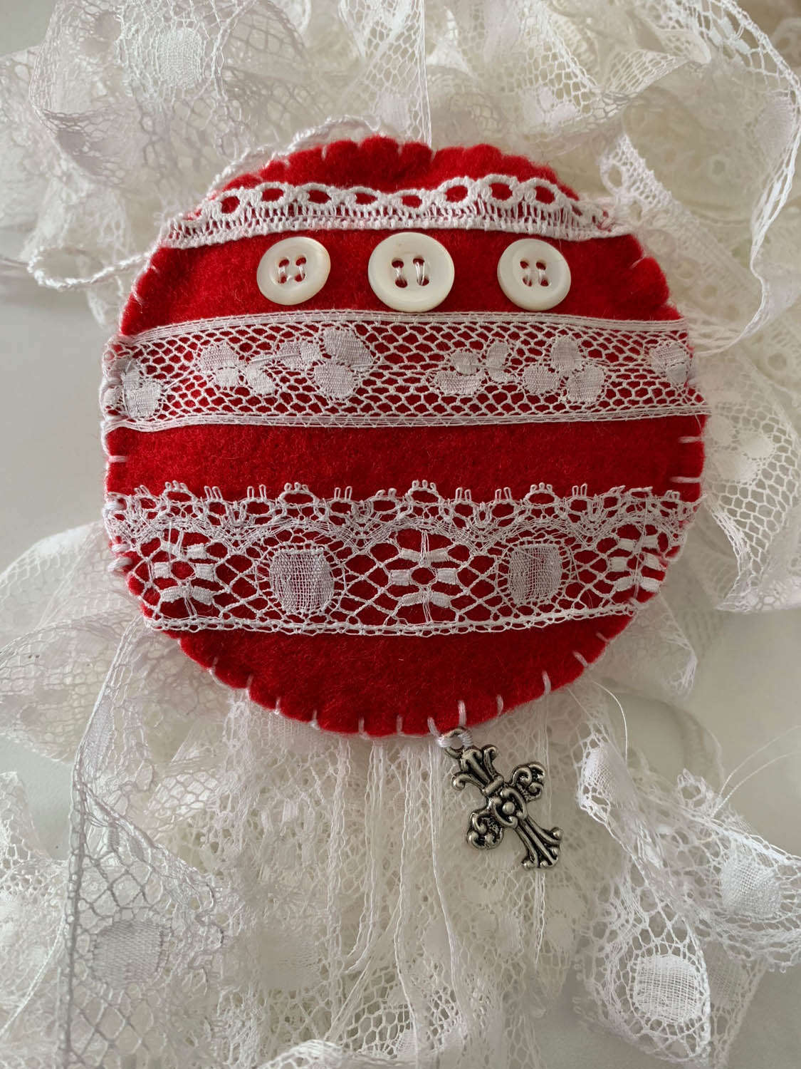 Finished hand made lace-embellished red felt Christmas ornament.