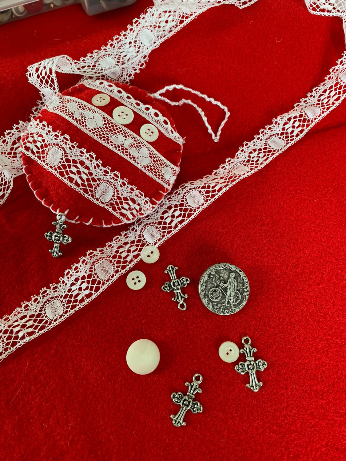 finished lace embellished ornament on top of red felt with scattered extra lace trims buttons and charms