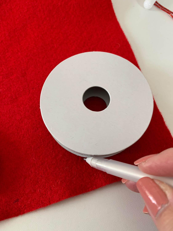 pen tracing ribbon reel circle shape onto red felt