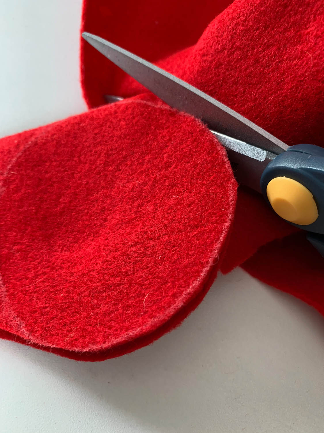 two layers of red felt being cut into circles with scissors