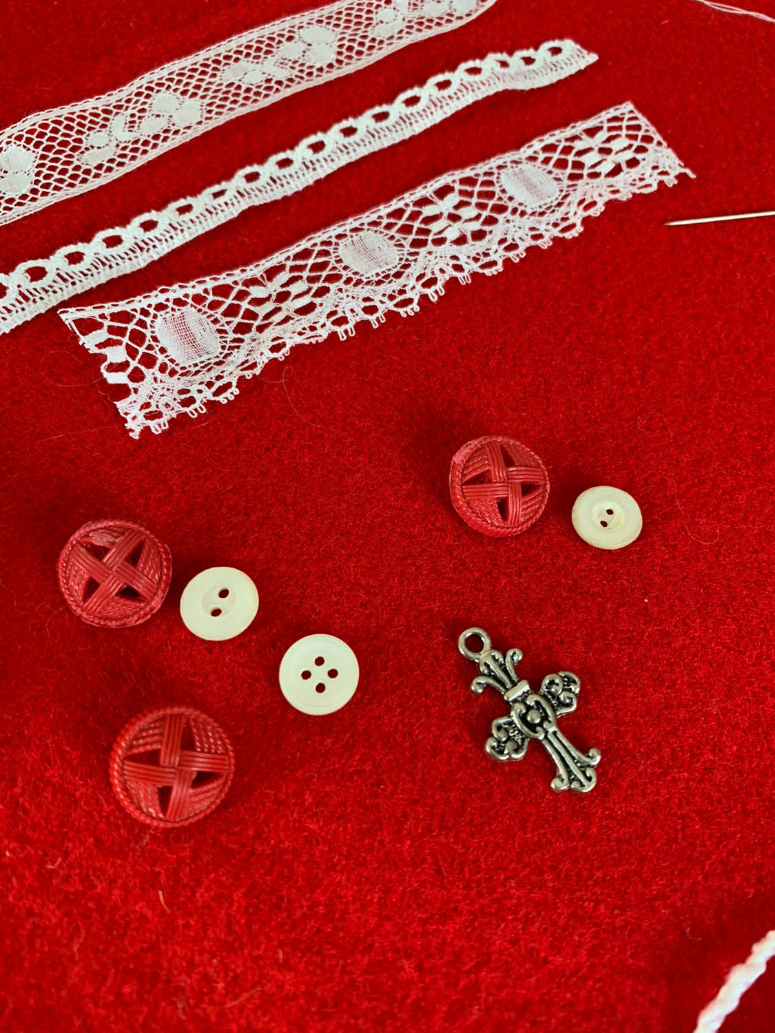 lace trims, buttons and charms atop red felt