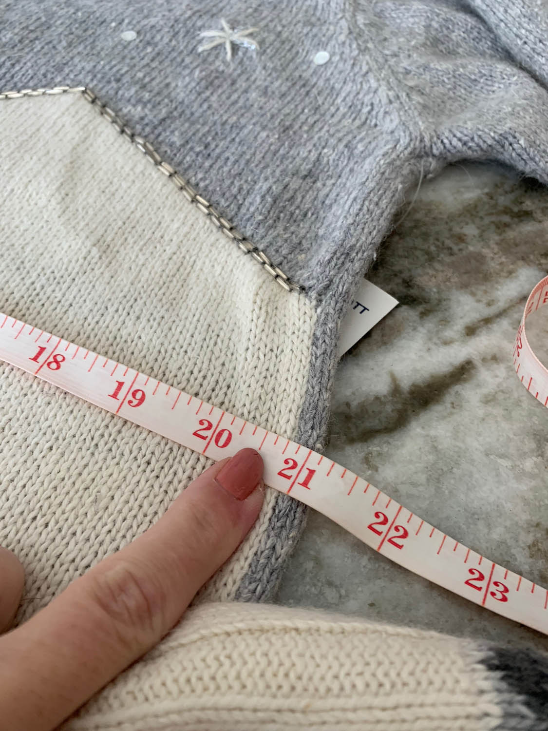 tape measure measuring sweater width for pillow