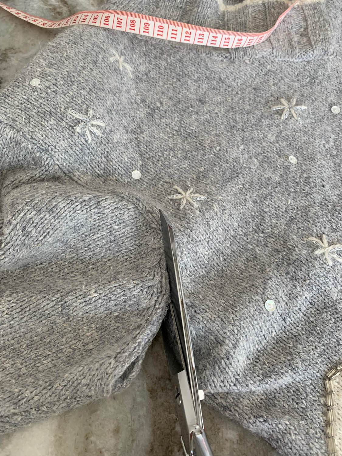 using sicissors to cut sleeve off of upcycled sweater for pillow