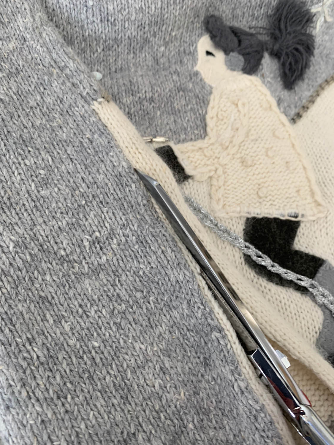 scissors cutting sweater down seam line for pillow top