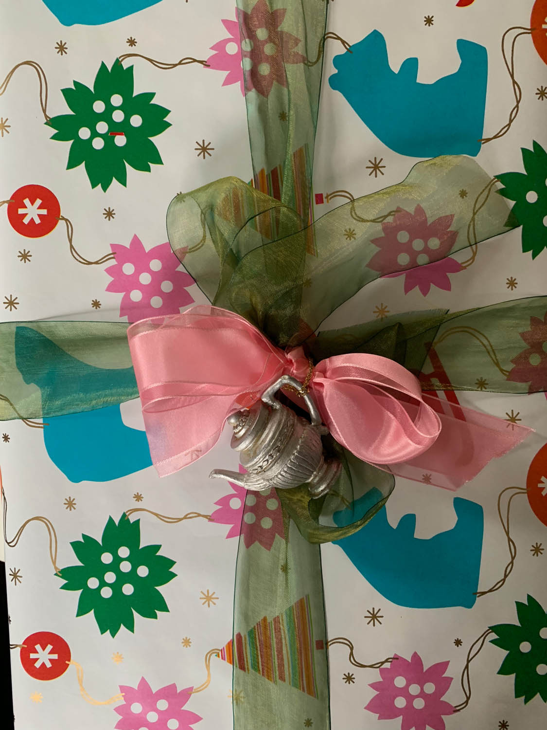 beautifully wrapped gift with ribbon and tea pot ornament