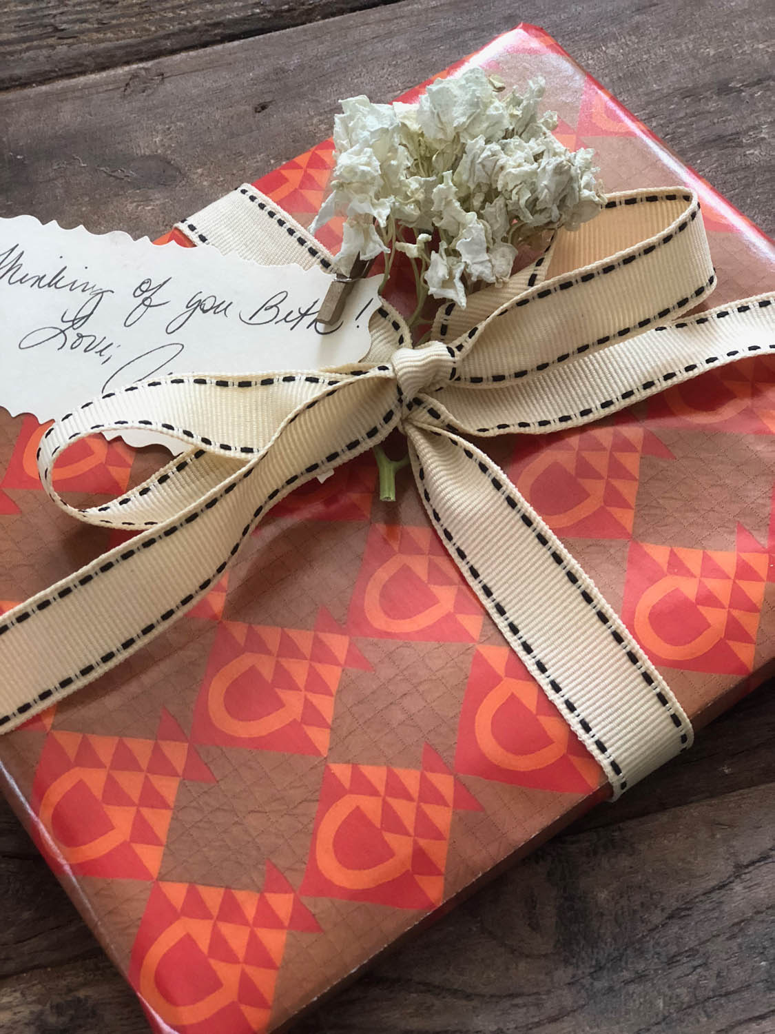 birthday gift wrapped in quilt basket paper with dried flowers and ribbon embellishments