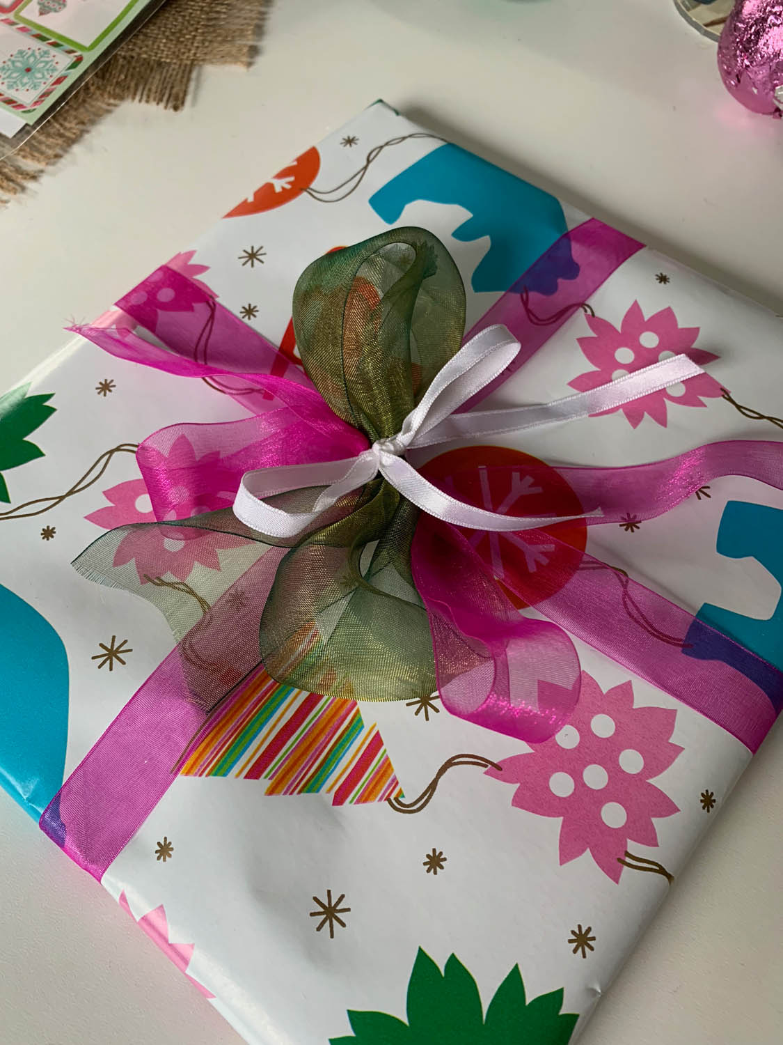 colorful wrapped gift tied with multiple ribbon sizes and colors