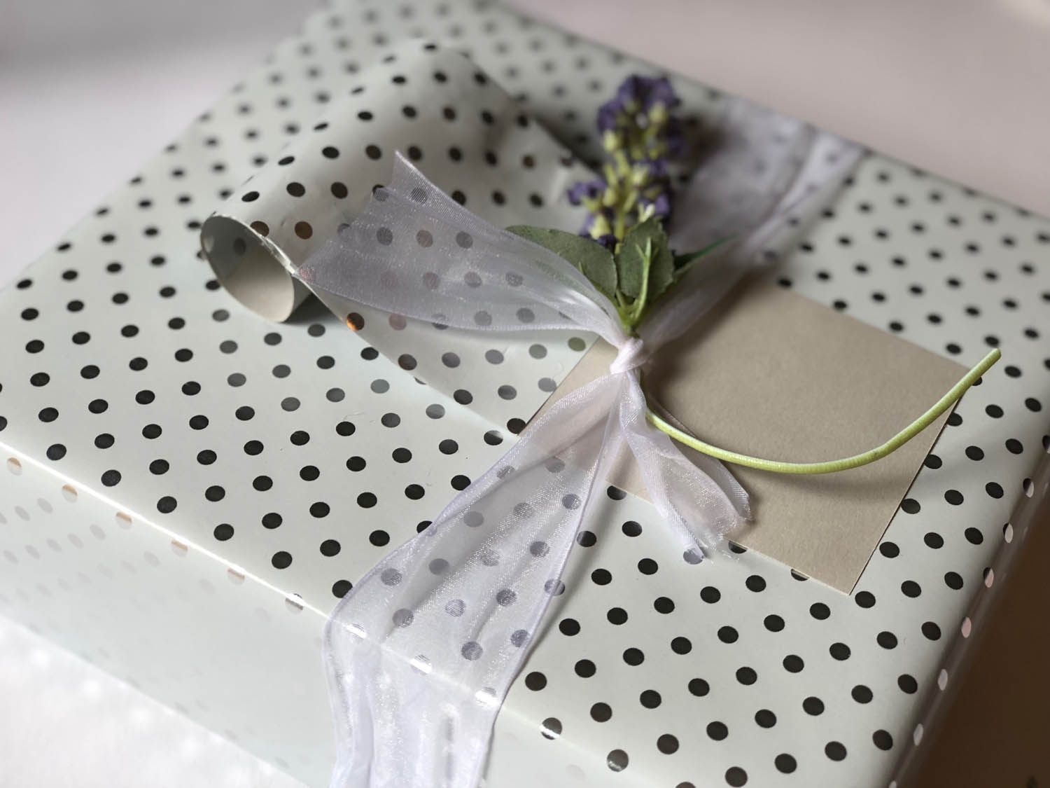 elegant gift wrap for a wedding present with paper scroll and floral pic embellishment