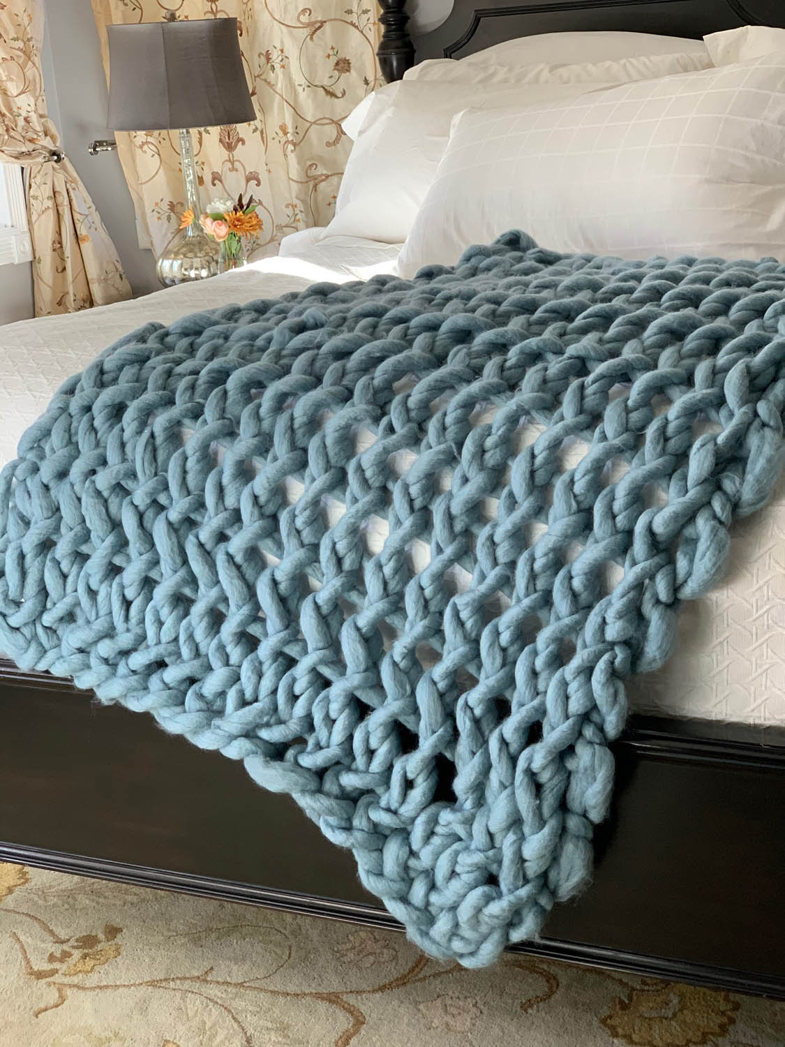 Finished DIY 1-hour arm-knitted throw in Free Spirit yarn by Loops & Threads in Dusty Blue.