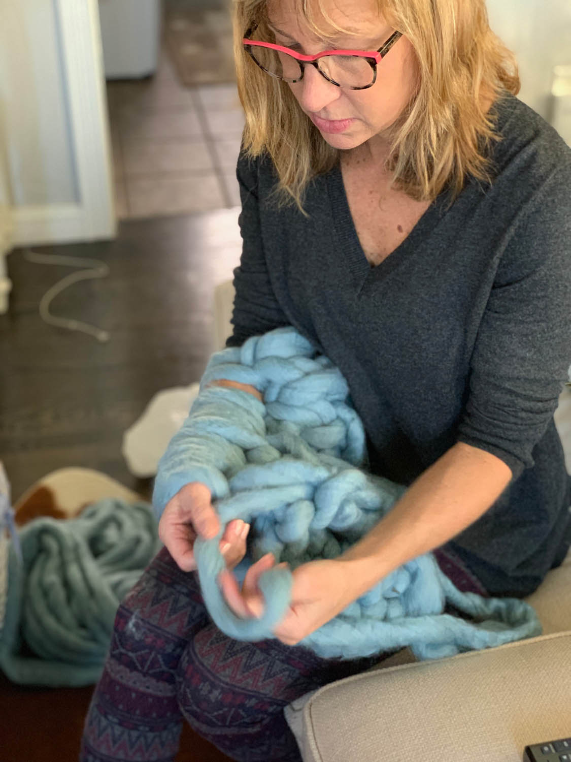 Woman working arm-knitted stitches for a jumbo yarn throw in 1 hour