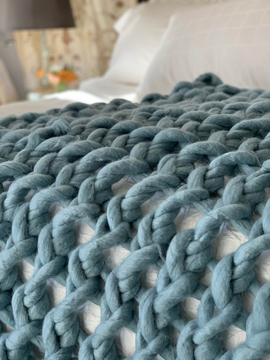 Finished arm-knitted throw on a bed