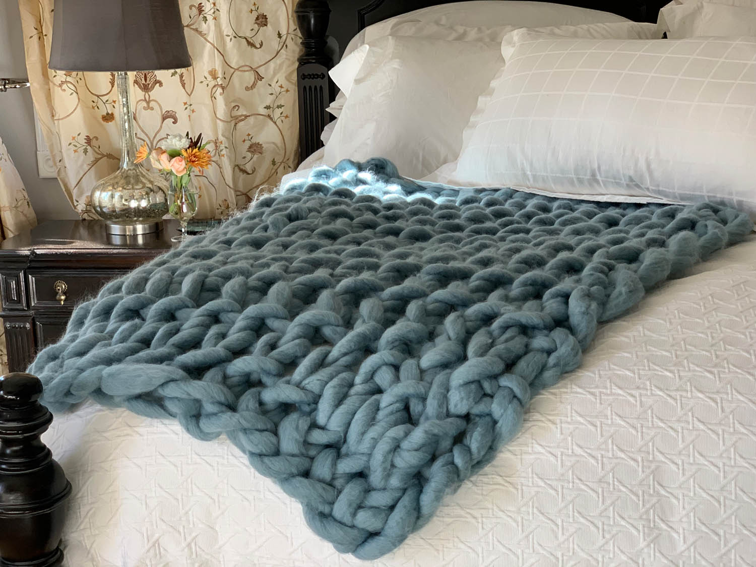 Finished 1 Hour Easy Arm-Knitted Throw in dusty blue on a white bed