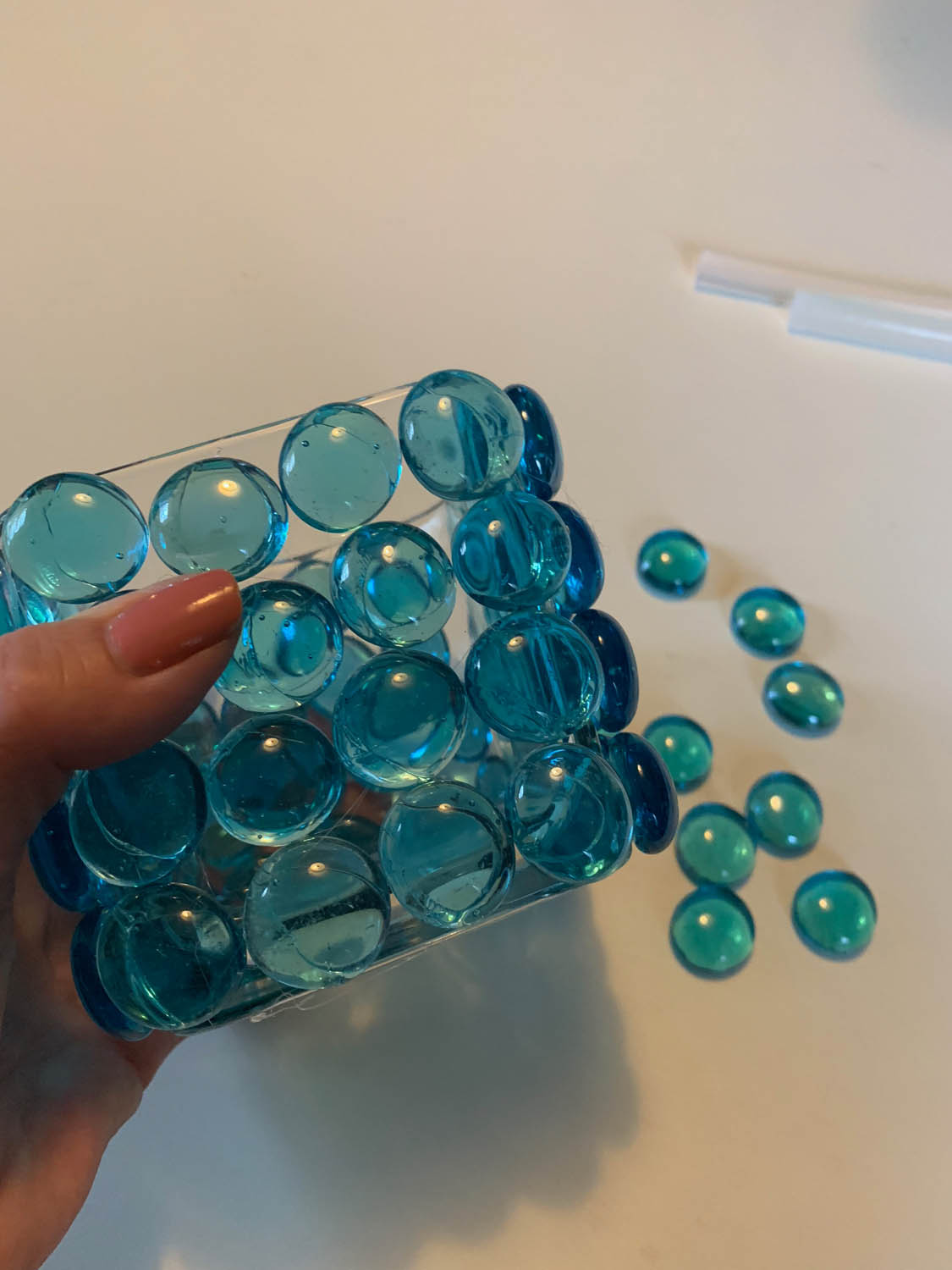 hand holding dollar store glass vase covered with flat-bottom blue marbles applied with a hot glue gun