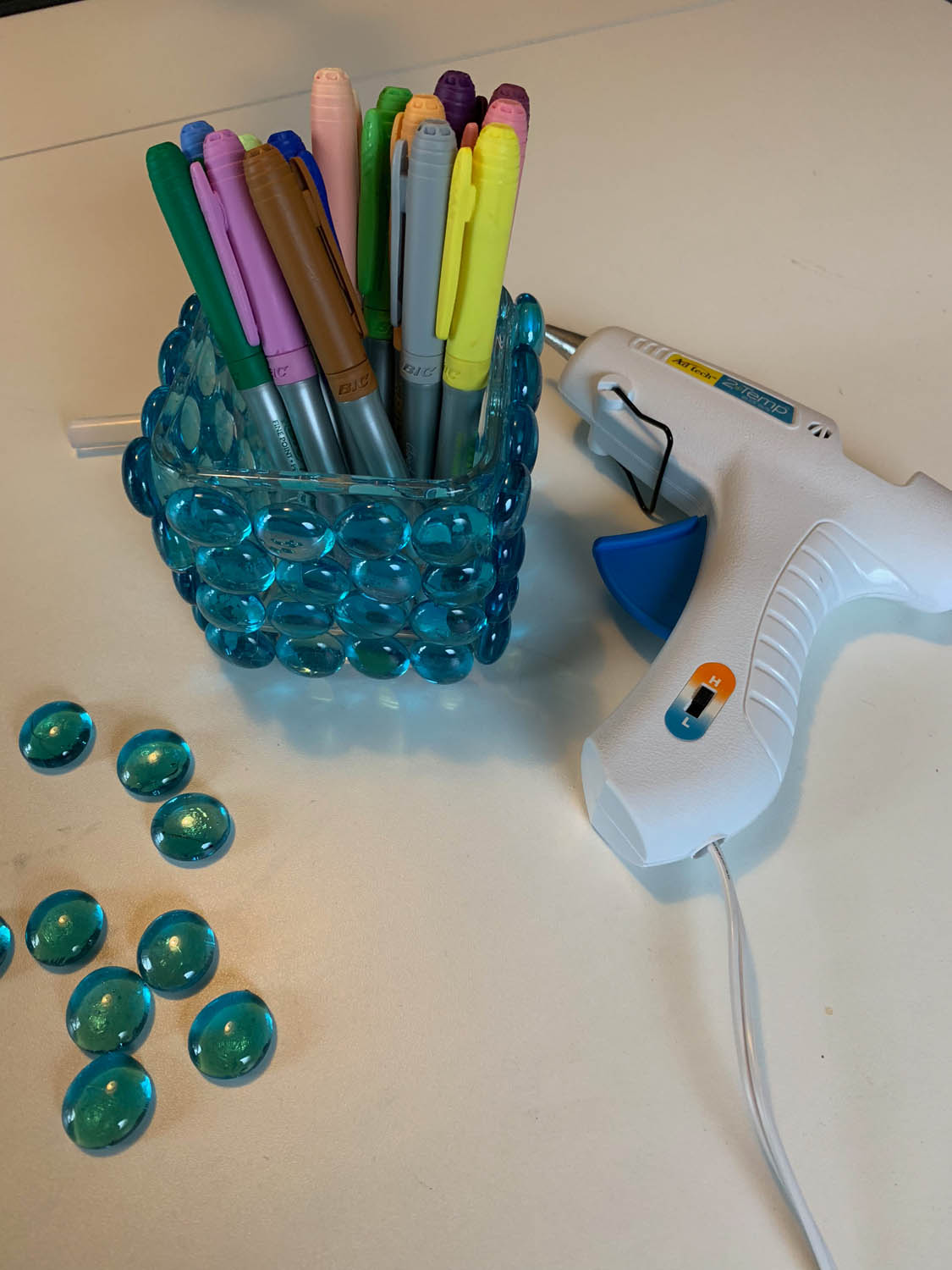 hand made diy dollar store vase covered with blue marble beads and filled with markers next to a hot glue gun