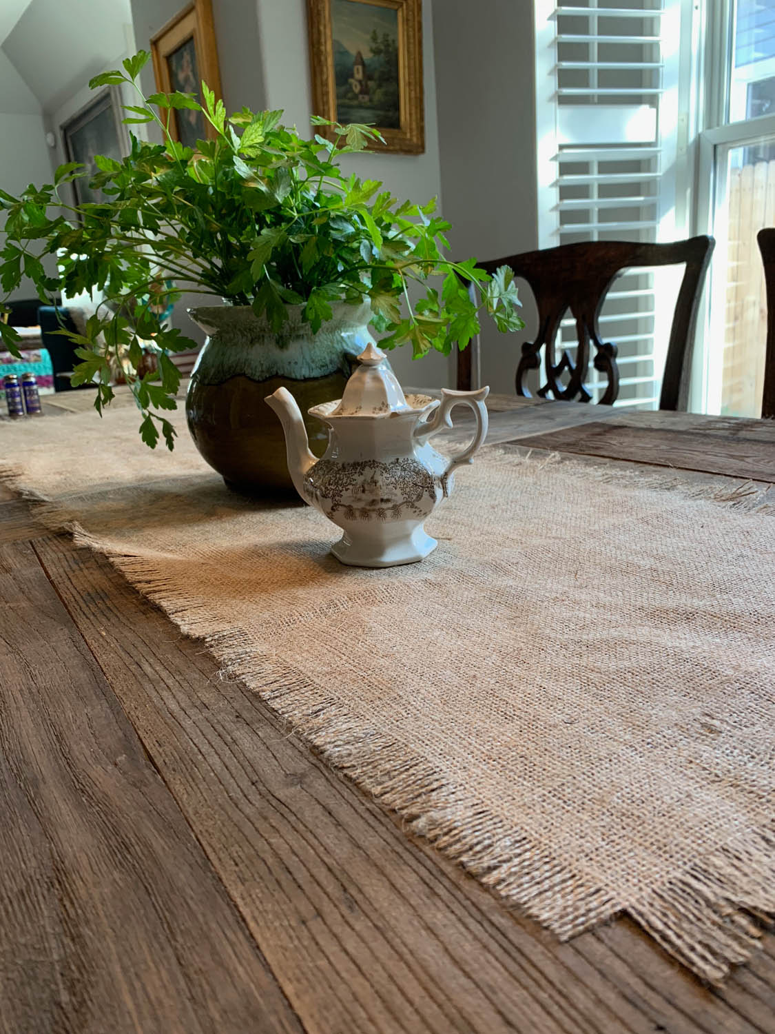 Plant and teapot on burlap table runner on rustic tabletop