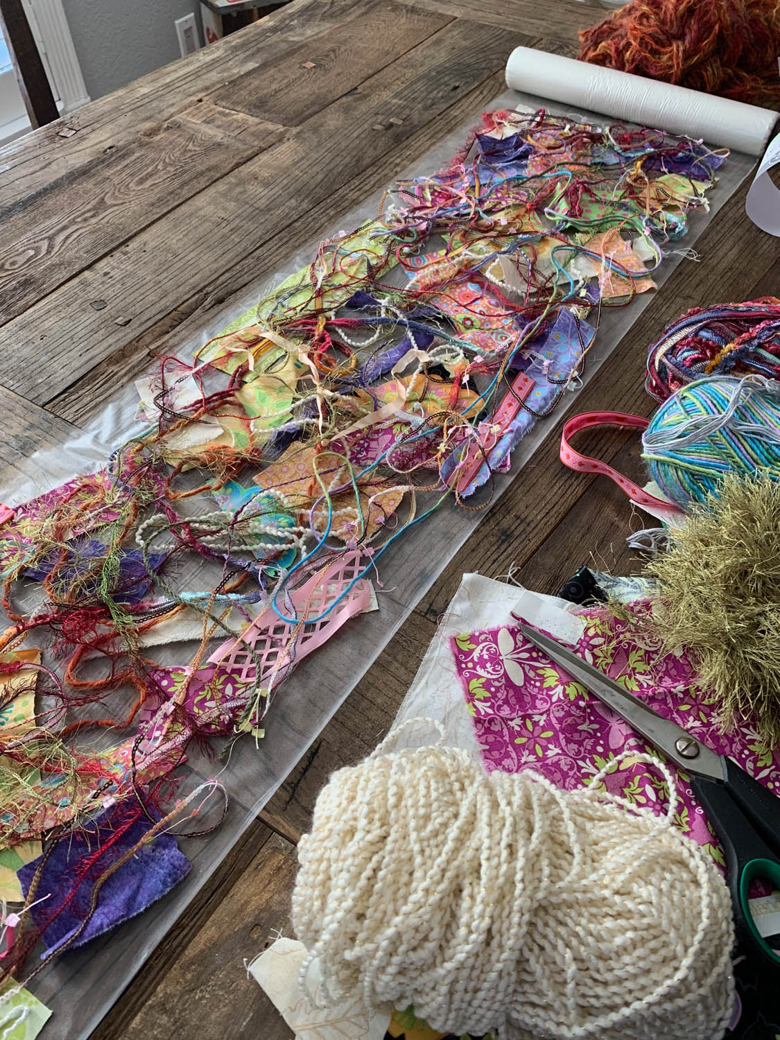 fiber scraps and bits atop Sulky Solvy to make upcycled fiber art table runner