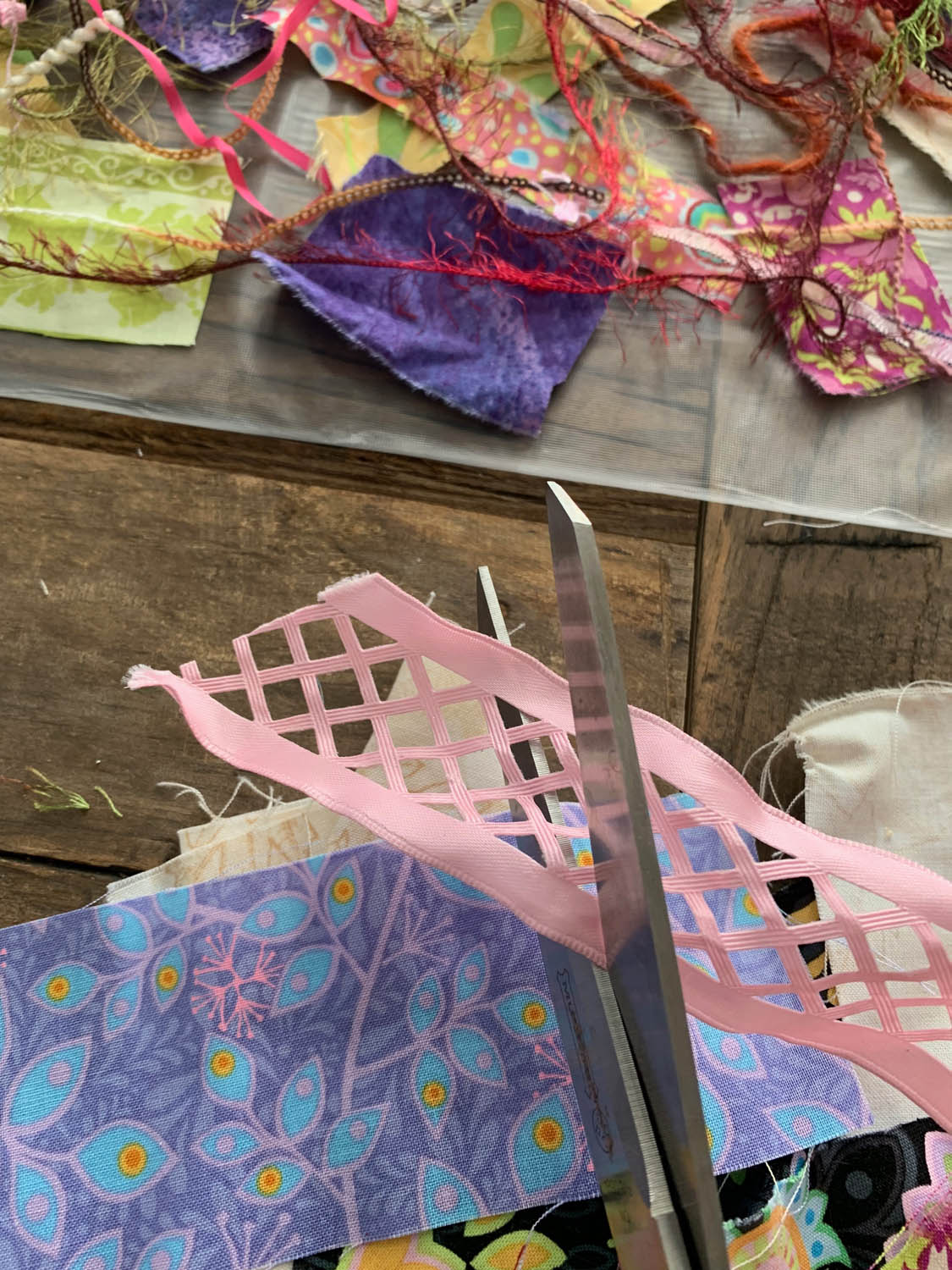 scissors cutting scraps of ribbon for upcycled artistic thread-quilted table runner