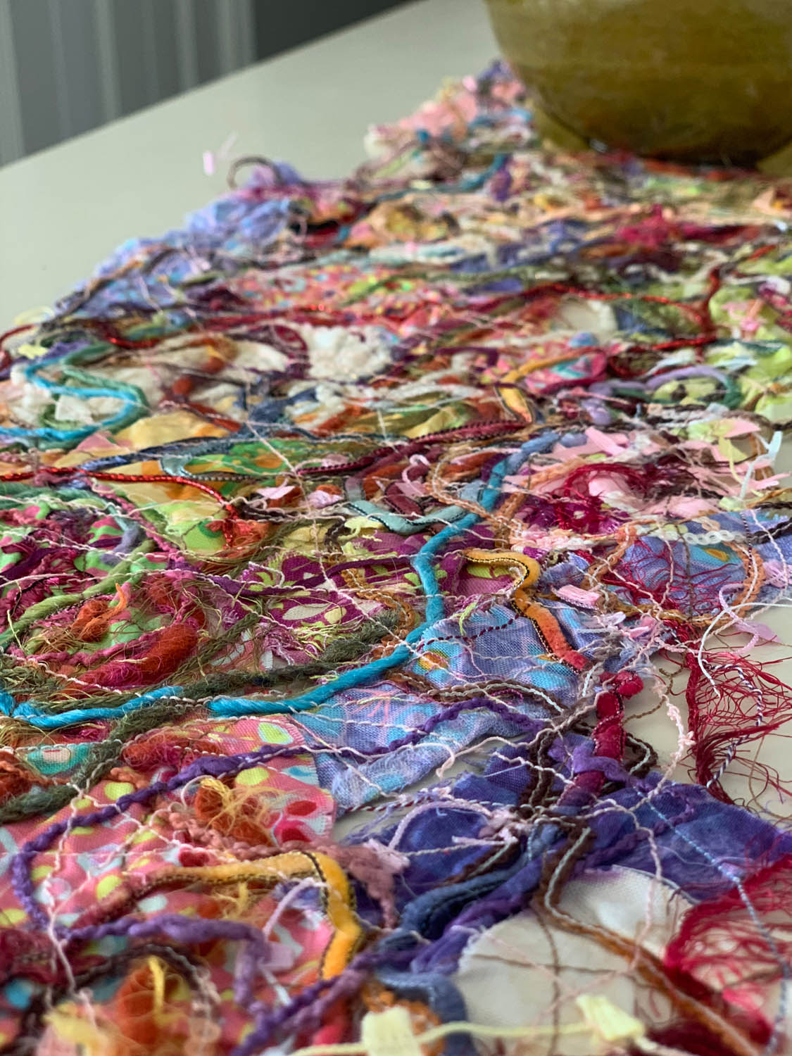 close up image of assorted upcycled fibers in the finished thread-quilted fiber art table runner