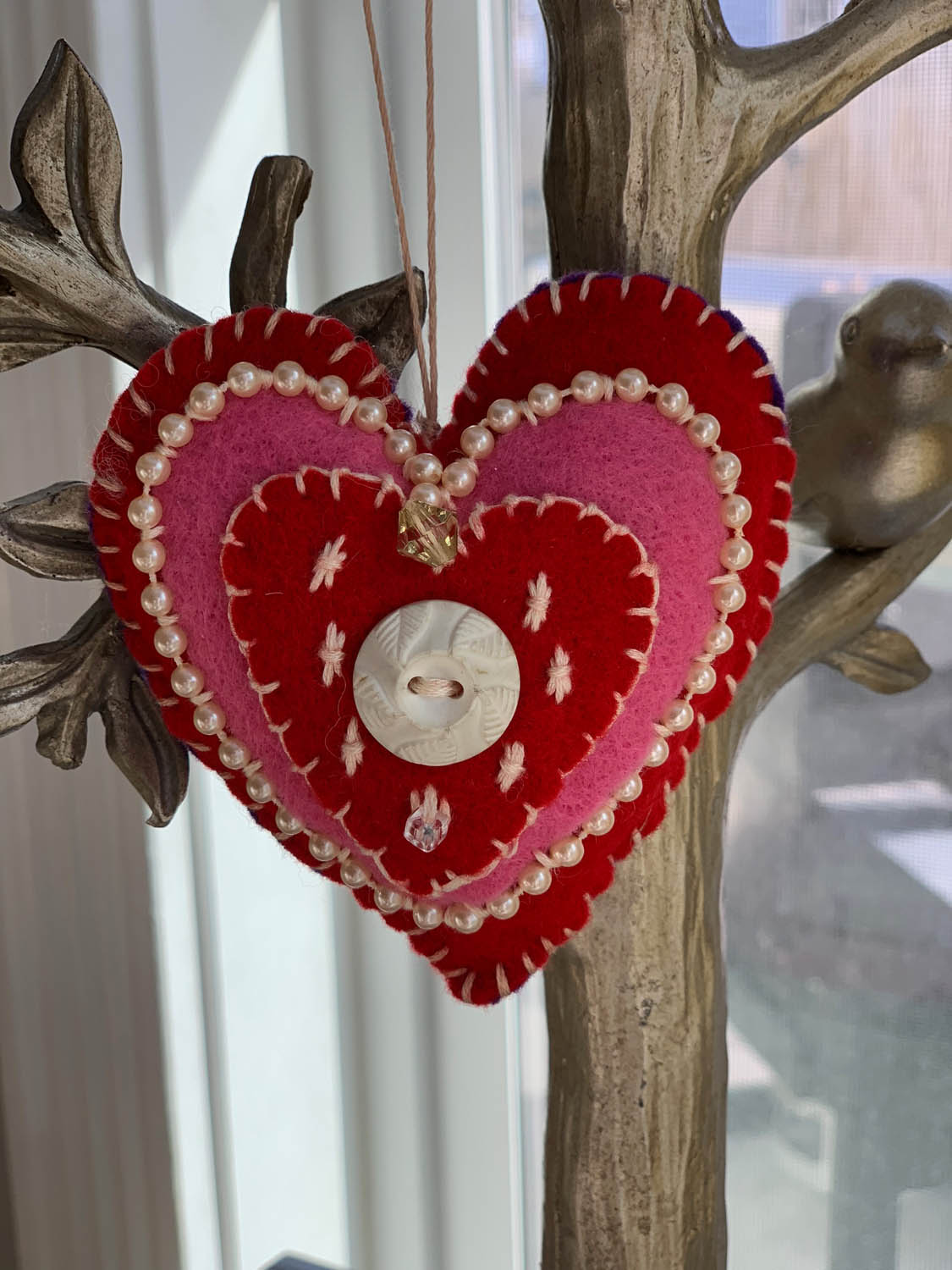 Handmade valentine heart ornament in red and pink felt with bead trim and embroidery