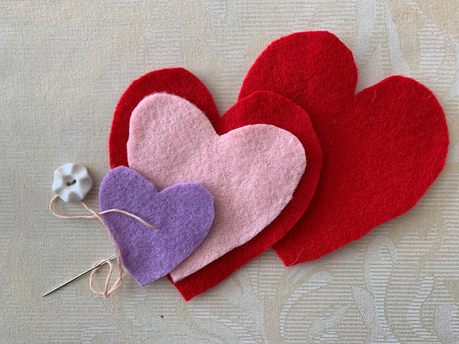felt heart shapes in purple pink and red with button and embroidery needle