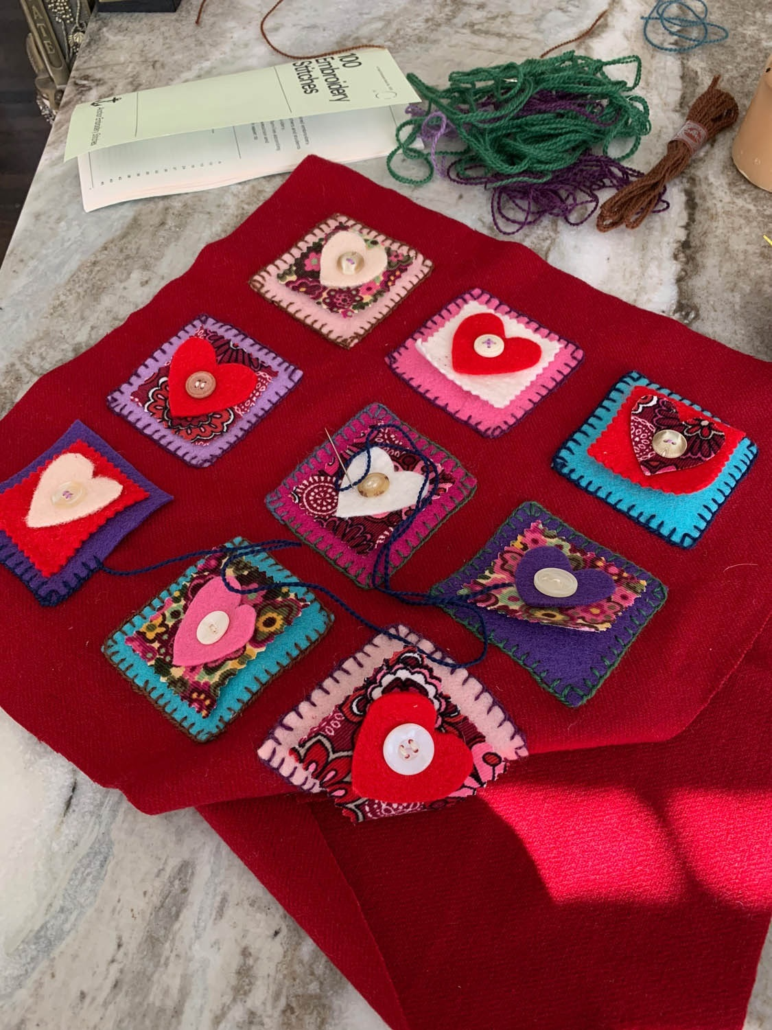 hand embroidered nine-patch heart felt squares on a pillow front