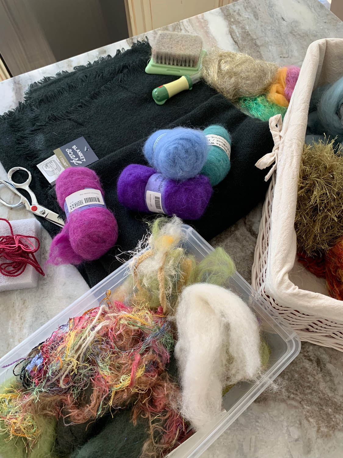 roving and yarn fibers in bins with pre-made ladies black woven shawl