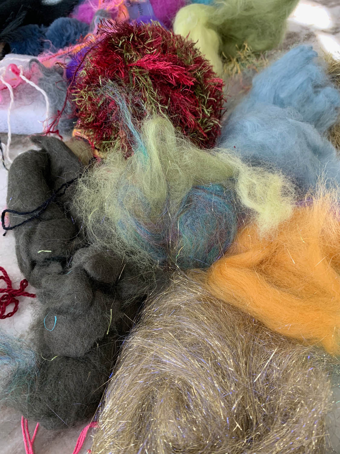stash of roving and yarn fibers for felting a pre-made fashion ladies shawl