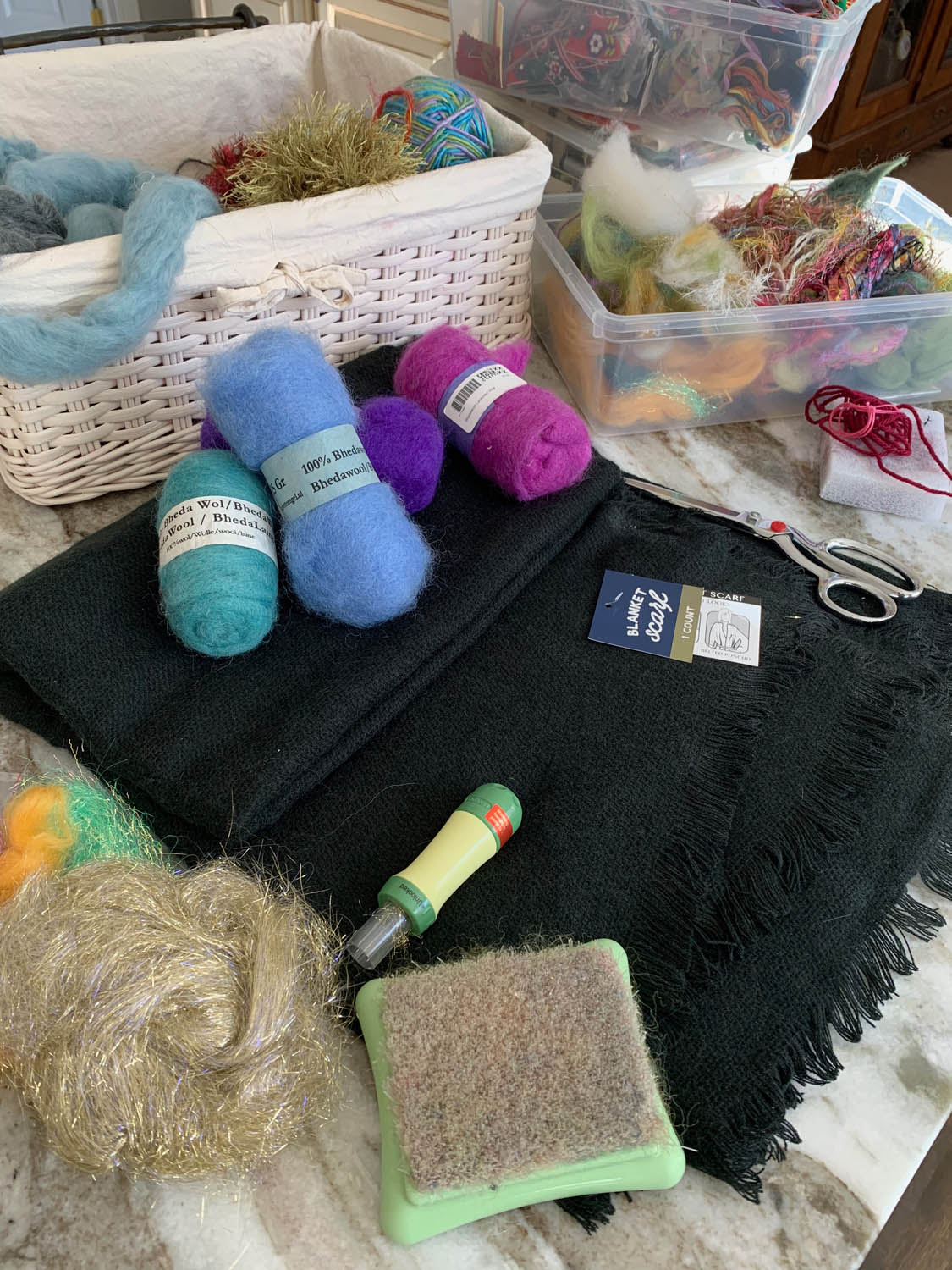 bins of roving and yarn fibers with needle felting tools