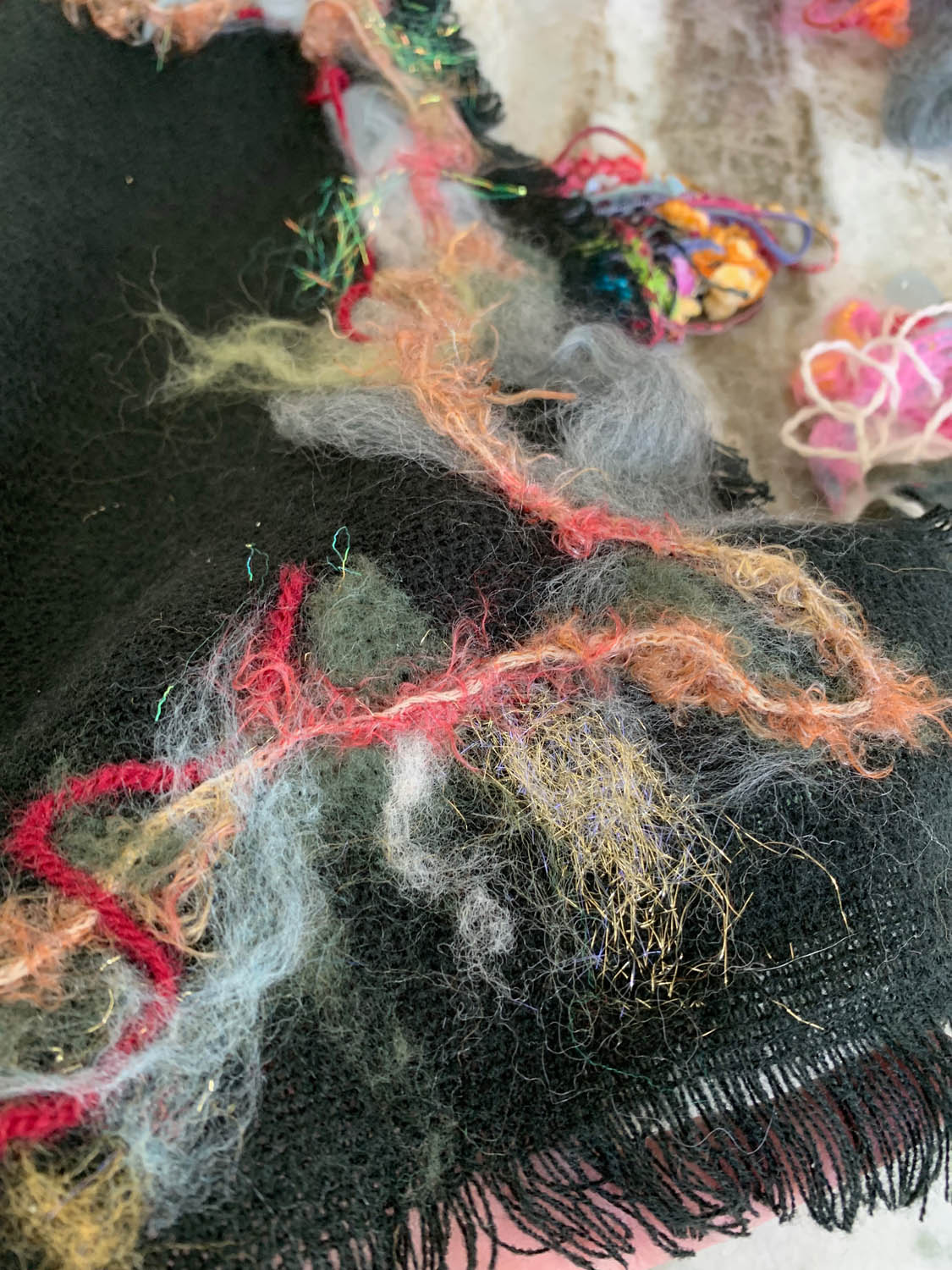 fibers and yarns being placed on pre-made scarf getting ready to needle felt in place
