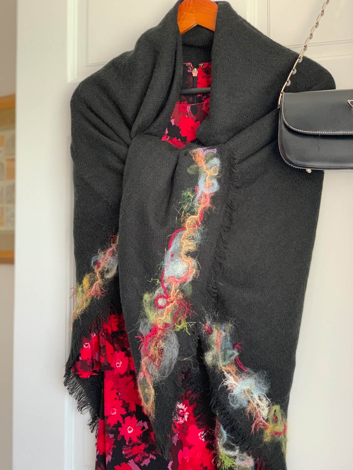 Needle felted fibers embellishing the border of a pre-made shawl wrap over a dress hanging on a door