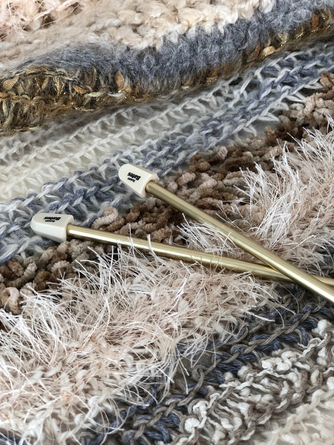 knitting needles atop hand knit winter white yarn throw or shawl
